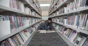 Studentzitting op vloer in bibliotheek, lezingsboek De draaien boeken pagina's Midleschot stock video