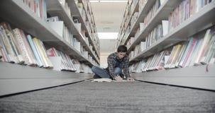 Studentzitting op vloer in bibliotheek, lezingsboek De draaien boeken pagina's stock footage