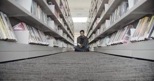 Studentzitting op vloer in bibliotheek, lezingsboek Verticale vorm, midle vqiew stock footage