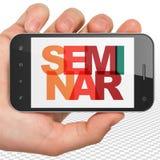 Studera begrepp: Hand som rymmer Smartphone med seminarium på skärm Arkivbild