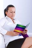 Studerande bok för attraktiv brunett Arkivfoton