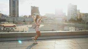 Studet alegre feliz de la mujer que corre en calles urbanas de la ciudad y que disfruta de vida en el fondo de la puesta del sol almacen de metraje de vídeo