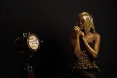 金衣裳的美丽的年轻非洲摆在studi的妇女和辅助部件握手临近面孔 免版税库存图片