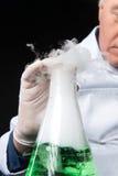 Studi professionali del clinico in laboratorio facendo uso della boccetta Immagine Stock