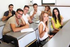 Studiando con i pollici su nella stanza di classe Immagini Stock