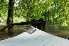 Studiando con un libro nel parco, occhiali da sole sulla tavola immagini stock