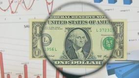 Studie av en sedel en dollar som ökar med hjälpen av ett förstoringsglas stock video