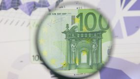 Studie av en sedel hundra euro som ökar med hjälpen av ett förstoringsglas arkivfilmer