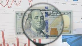Studie av en sedel i hundra dollar som ökar med hjälpen av ett förstoringsglas stock video