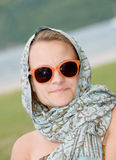 Studie av en ung kvinna med en halsduk och solglasögon arkivfoto