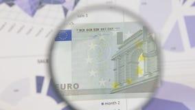 Studie av ett euro för sedel som fem ökar med hjälpen av ett förstoringsglas lager videofilmer