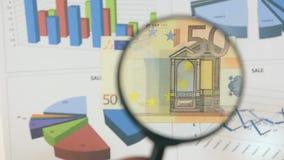 Studie av ett euro för sedel som femtio ökar med hjälpen av ett förstoringsglas arkivfilmer