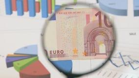 Studie av ett euro för sedel som tio ökar med hjälpen av ett förstoringsglas stock video