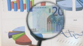 Studie av ett euro för sedel som tjugo ökar med hjälpen av ett förstoringsglas lager videofilmer
