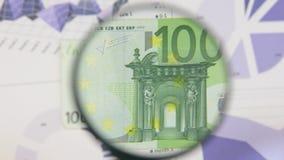 Studie einer Banknote hundert Euro, erhöhend mithilfe einer Lupe stock footage