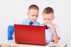 Studie over computer twee jongens op school stock foto