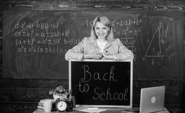 Studie und Bildung Moderne Schule Kursteilnehmer der ?lteren Kategorie f?hrt die ersten Lektionkinder Lehrer mit Wecker an der Ta lizenzfreie stockbilder
