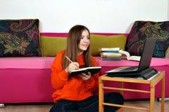 Studier för tonårs- flicka med en bok och en bärbar dator royaltyfria bilder