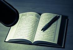 Studieren von Quran nachts hinter Schreibtisch lizenzfreie stockfotografie
