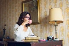 Studierender und trinkender Kaffee der Frau auf Hippie-Schreibtisch Stockfoto