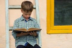 Studierendes Buch des Jungen Stockbilder