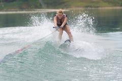 Studieridning för ung kvinna som wakeboarding på sjön Arkivbilder