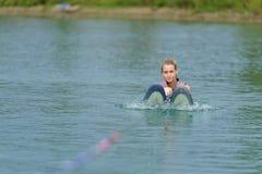 Studieridning för ung kvinna som wakeboarding på sjön Royaltyfria Bilder