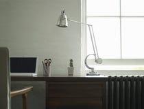 Studieskrivbord med bärbara datorn och lampan Arkivbild