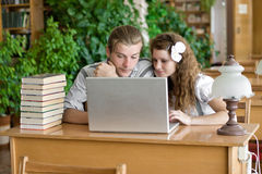 Studing Books & Laptop. Two students with laptop and books in library Royalty Free Stock Photography