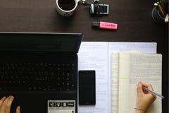Studing och writig på ett skrivbord Royaltyfri Fotografi