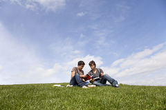 Studing in outdoor. Two young student reading books at the school park Royalty Free Stock Image