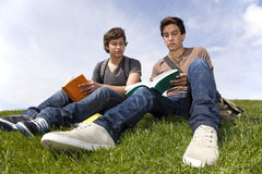 Studing in outdoor. Two young student reading books at the school park Stock Photos