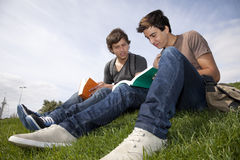 Studing in outdoor. Two young student reading books at the school park Royalty Free Stock Images