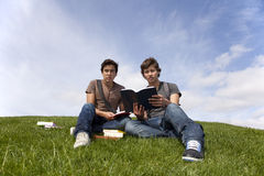 Studing in outdoor. Two young student reading books at the school park Stock Image
