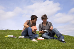 Studing in outdoor. Two young student reading books at the school park Stock Photography