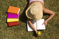 Studing at the school grass. A student relaxing at the grass of the school park (the pages in the book are my self printed Stock Image