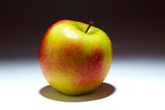 Studio apple. Fresh red and yellow apple on a grey gradient background Royalty Free Stock Photography