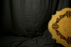 Studio backdrop with old wooden medallion. A black cloth backdrop fills the image with a portion of a large antique golden medallion seen on the right Stock Images