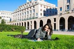 Studio/che sorride studente/della ragazza su un prato inglese dell'erba verde Immagine Stock