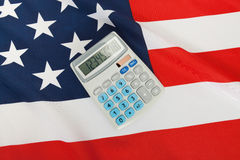 Studio close up shot of ruffled national flag with calculator over it - United States of America Stock Images