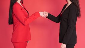 Two business partners shaking hands in agreement on red background. Studio close up of unrecognizable successful businesswomen in red and black suits shaking stock footage