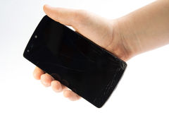 Studio closeup of a hand, holding a smartphone with cracked screen Stock Image