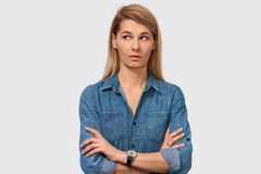 Studio closeup portrait of attractive young female with amazed look, cross hands together, concentrated aside, waits for something royalty free stock photography
