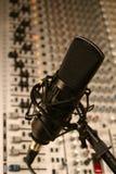 Studio Condenser Microphone. A black studio condenser mic in front of a sound board Stock Image