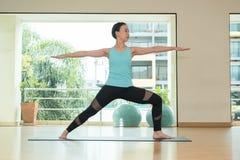 Studio de classe de yoga, pose faisante principale de la guerrière II de femme asiatique, Healt photos libres de droits