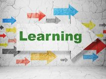 Studio del concetto: freccia con l'apprendimento sul fondo della parete di lerciume Fotografia Stock Libera da Diritti