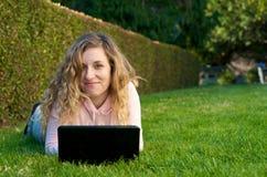 Studio dell'allievo esterno con il computer portatile Fotografia Stock