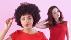 Studio der jungen Frauen lokalisiert auf rosa Frauen ` s Tagesrührendem Haar stock video
