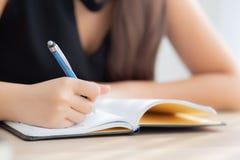 Studio di seduta della donna asiatica della mano del primo piano ed imparare scrivendo taccuino e diario sulla tavola nel salone  immagine stock libera da diritti