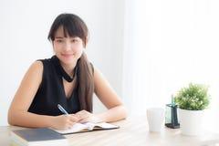 Studio di seduta sorridente della bella giovane donna asiatica ed imparare scrivendo taccuino e diario nel salone a casa fotografie stock libere da diritti